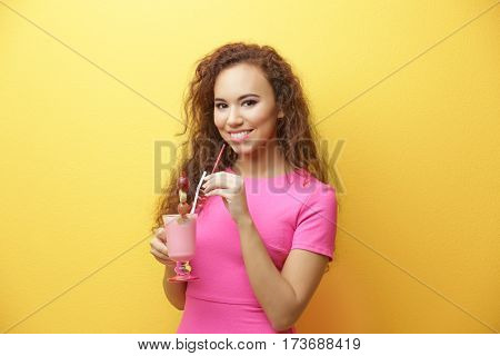 Young beautiful woman with milk shake on yellow background