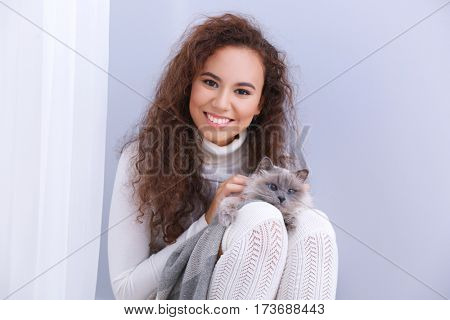Beautiful young woman with cat on lap
