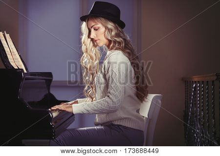 Beautiful woman at piano in room