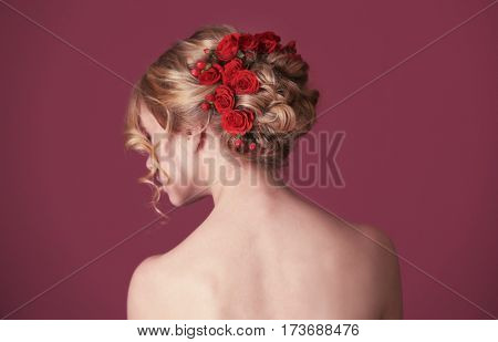 Beautiful young woman with flowers in hair on color background