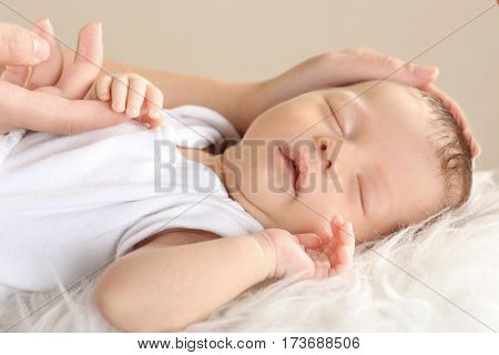 Cute sleeping baby with mother at home, closeup