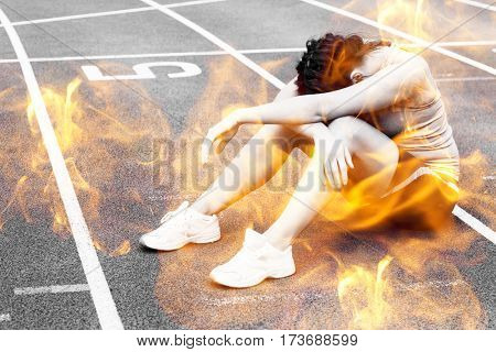 Fire flames against tensed sporty woman sitting on the running track