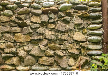 Wall built of large old stones, a fence of stones, stone texture close-up.
