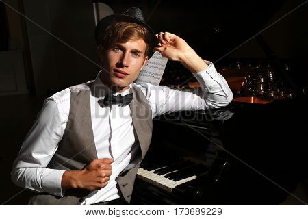 Young musician posing near piano