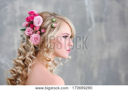 Beautiful young woman with flowers in hair on blurred background