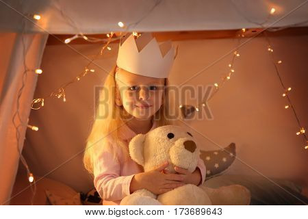 Cute little girl sitting in hovel with cuddly toy poster