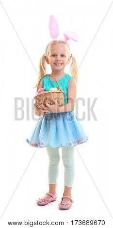 Cute little girl with bunny ears and basket full of Easter eggs on white background