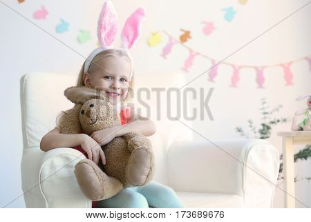 Cute little girl with bunny ears and cuddly toy sitting in arm-chair at home