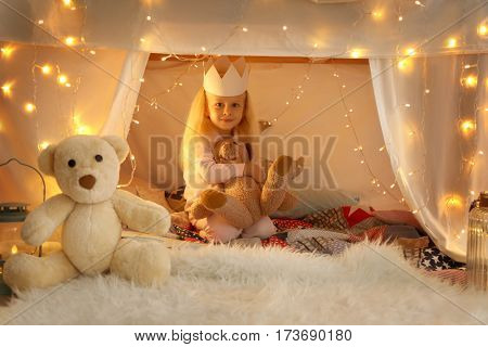 Cute little girl sitting in hovel with cuddly toy