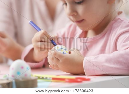 Mother and little girl decorating Easter eggs