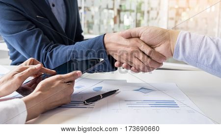 Business Handshake Of Two Men Demonstrating Their Agreement To Sign Agreement Or Contract Between Th