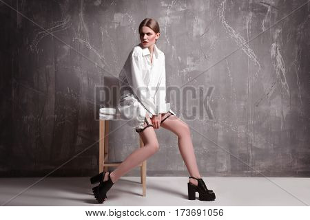 Young extravagant model sitting on chair near grunge wall
