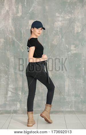 Beautiful young woman in security uniform standing near grunge wall