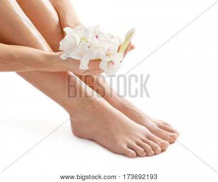 Female legs and hands with flowers on white background