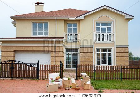 No people image of expensive detached cottage house with built-in garage and green lawn ready for sale, fully furnished: furniture and cardboard boxes standing outside in driveway