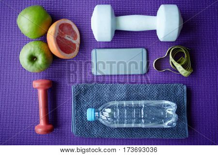 Top view of fitness equipment laid out on yoga mat: fruits, measuring tape, dumbbells and bottle of  fresh water representing dieting concept