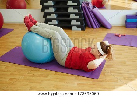 Side view  portrait of young obese woman working out in gym: using fitness ball for sit ups  with effort to lose weight