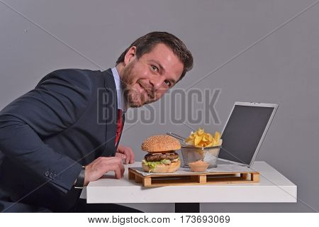 Young businessman working on computer laptop while eat burger and fried potatoes.