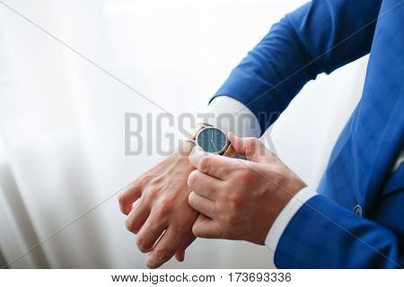 Businessman checking time on his wristwatch. men's hand with a watch