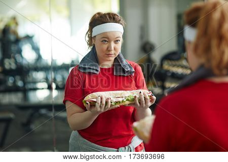 Portrait of cute overweight woman looking skeptical in mirror holding huge fat sandwich while working out in gym, enduring the struggle of weight loss dieting