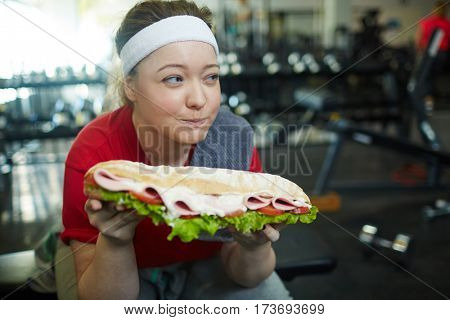 Portrait of cute overweight woman looking away secretly wanting to eat huge fat sandwich while working out in gym, struggling to keep fit