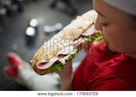 High angle shot of young overweight woman eating big greasy fattening sandwich at work out in gym, concept of food obsession