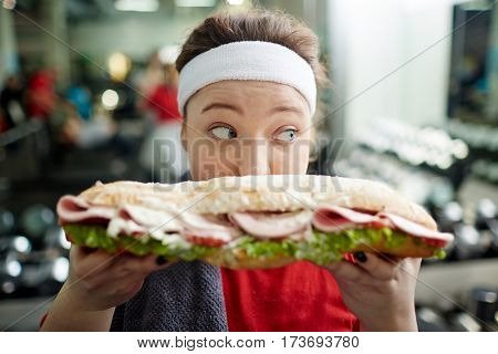 Closeup portrait of young  overweight woman holding big fattening sandwich in front of her face, eating it in secret and looking around cautiously, covered in smudges of mayo after training in gym