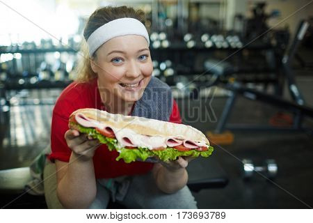 Portrait of cute plump woman smiling happily to camera wanting to eat huge sandwich while working out in gym