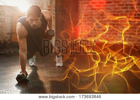 Abstract orange glowing black background against focused man lifting dumbbell