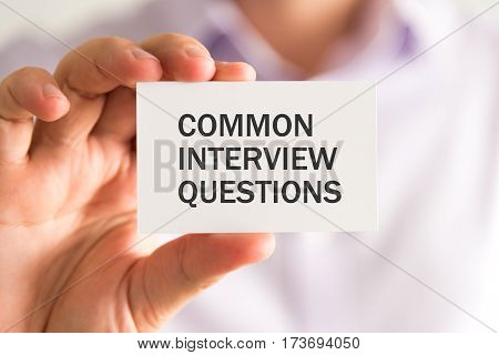 Businessman Holding A Card With Common Interview Questions Message