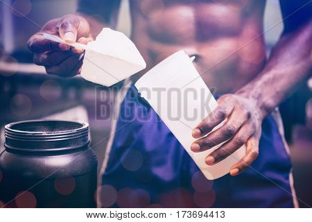 Glowing background against midsection of body builder holding scoop of protein mix