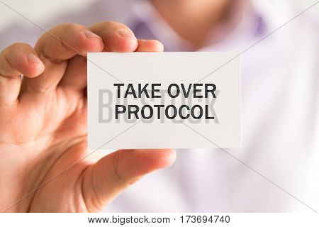 Businessman Holding A Card With Take Over Protocol Message