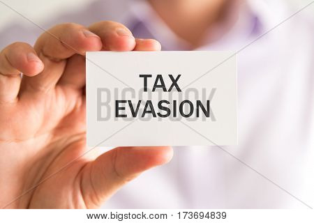 Businessman Holding A Card With Tax Evasion Message