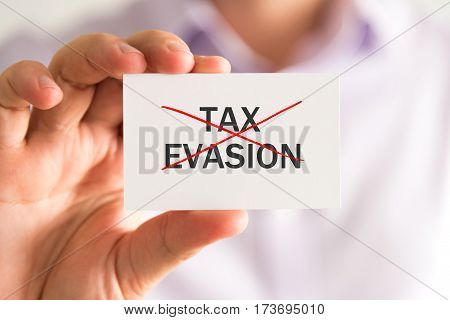 Businessman Holding A Card With No Tax Evasion Message