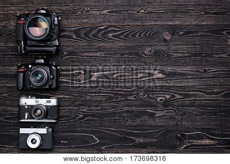Vintage and modern professional DSLR camera on dark wooden table.Top view