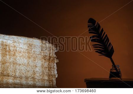 Silhouette of a quill pen and a backlit papyrus sheet on a brown blackground