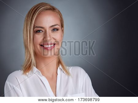 Portrait of a smiling middle aged Caucasian woman isolated against grey background