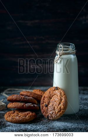 Oatmeal Cookies With Raisins, Chocolate And Milk In Bottles, Wood Background