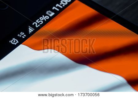 Smartphone on wooden background with 5G network sign 25 per cent charge and France flag on the screen.
