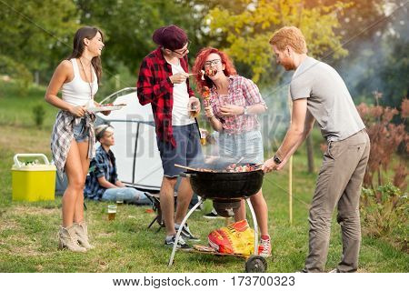 Man gives grilled skewers to curly ginger girl in camp ground