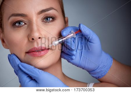 Woman having injection of  botox in lips,  beauty treatment