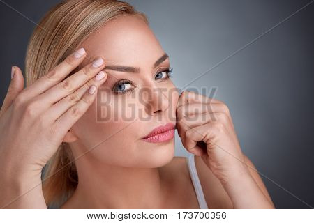 middle aged women try to see how to look that there are no wrinkles
