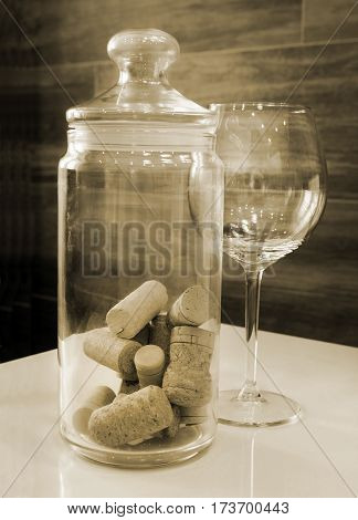 Wineglass and Bottle Corks in Glass Jar. Still life in sepia tone.
