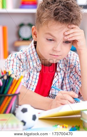 Young, sad boy sitting at desk in the classroom with his head in his hands
