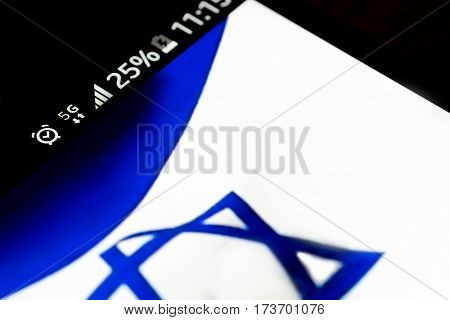 Smartphone on wooden background with 5G network sign 25 per cent charge and Israel flag on the screen.