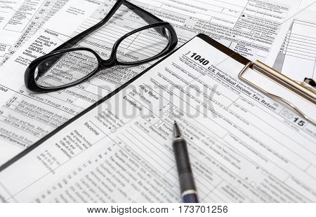 Tax form 1040 with pen and glasses.