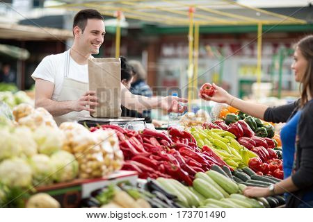 woman choosing fresh vegetables for measuring in grocery store