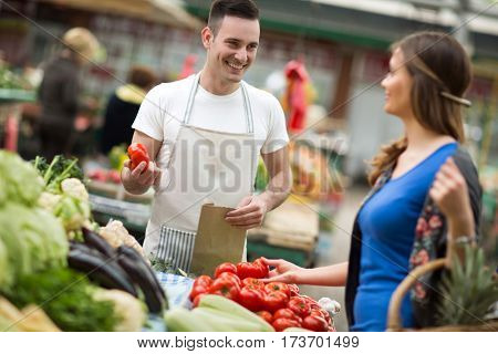 Young salesman smiling and holding vegetable at street market