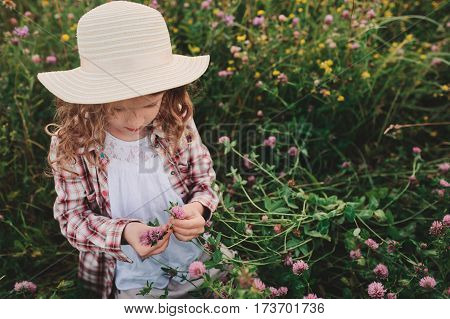 child girl in country style plaid shirt and hat relaxing on summer field and picking flowers