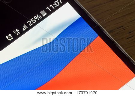 Smartphone on wooden background with 5G network sign 25 per cent charge and Russia flag on the screen.